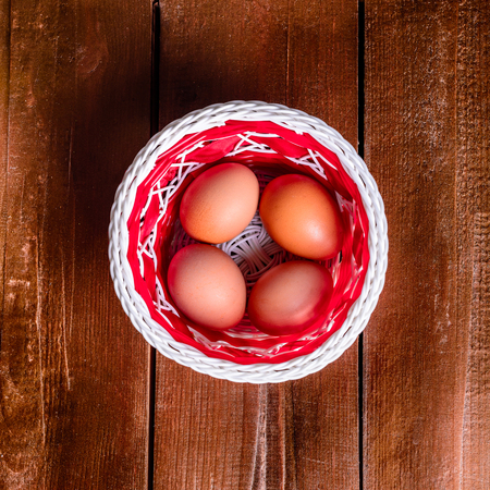 holydays: eggs in the basket on wood texture. Top view.