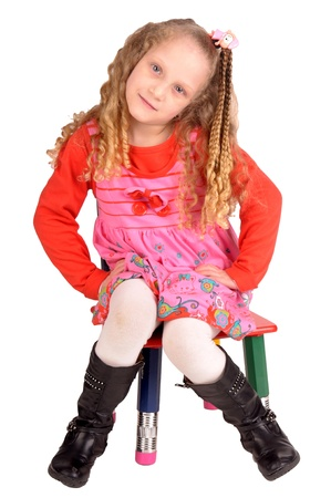 little girl sitting in a chair isolated in white Stock Photo - 19424758