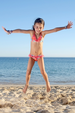 little girl jumping on the beach Stock Photo