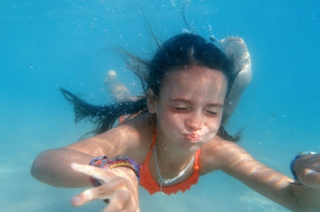 little girl swimming under water photo