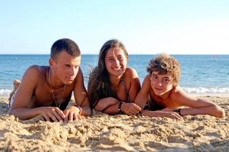teenage girl and boys posing in the beach photo