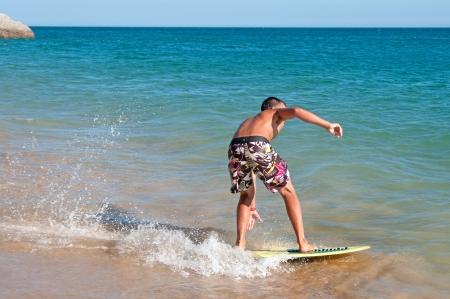 teenage boy surfing in the beach photo
