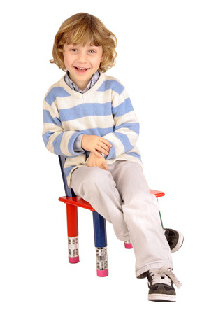 little boy sitting in a chair isolated in white photo