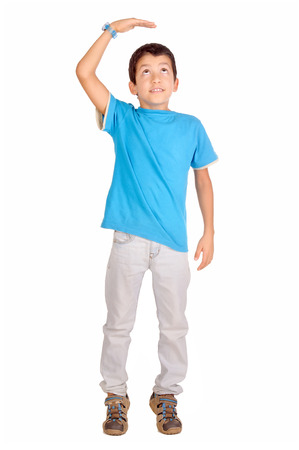 taller: little boy trying to be taller isolated in white