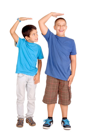 taller: little boys trying to be taller isolated in white