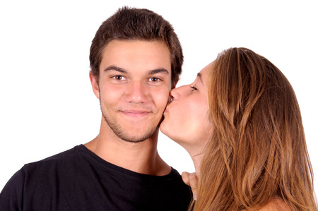 hot kiss: teenage girl kissing boy isolated in white