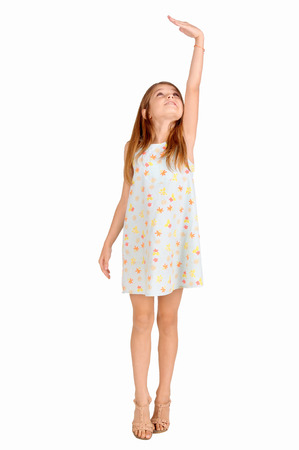 taller: little girl trying to be taller isolated in white