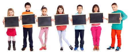 ni�os en la escuela: grupo de ni�os la celebraci�n de pizarra aislado en blanco Foto de archivo