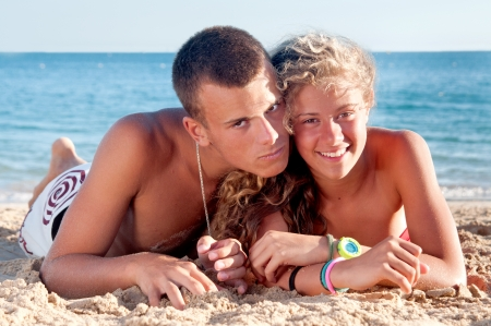 teenage girl and boy posing in the beach photo