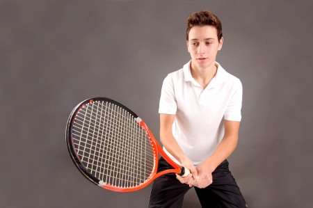 teenage boy playing tennis isolated in dark background photo