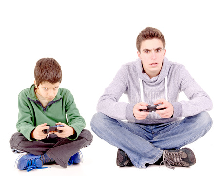joy pad: teenager and boy playing videogames isolated in white Stock Photo