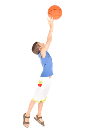 little boy playing basketball isolated in white photo