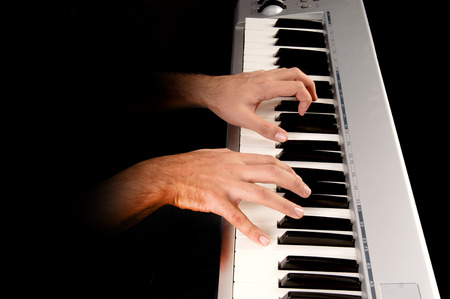 handsome young man playing the piano isolated in dark background photo