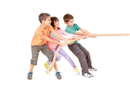 toiling: little kids playing pulling rope isolated in white Stock Photo