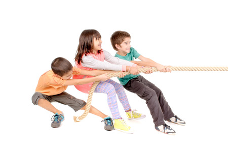 tugging: little kids playing pulling rope isolated in white Stock Photo