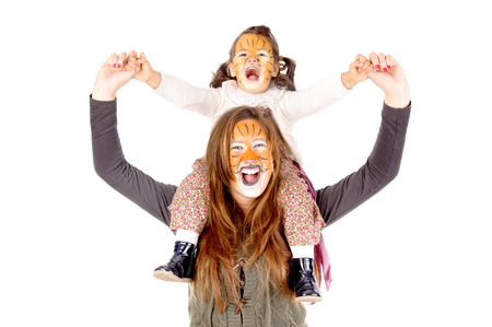 beautiful sisters with face painted as tigers isolated in white