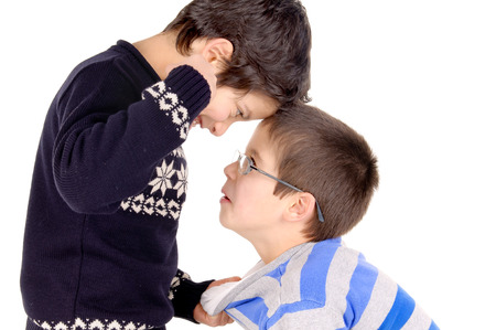 bullying: little boy bullying classmate isolated in white