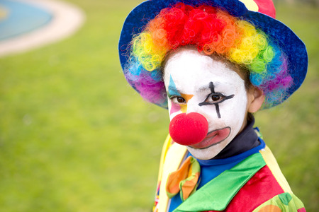evil clown: little girl dressed as a clown on halloween having fun together