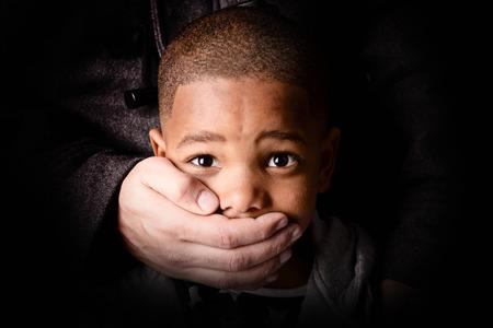 niño que está siendo secuestrado sobre fondo oscuro