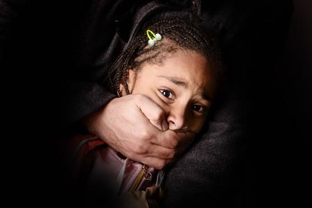maltrato infantil: niño que está siendo secuestrado sobre fondo oscuro