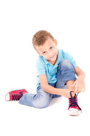 zapatos escolares: niño atar sus zapatos aislados en blanco Foto de archivo