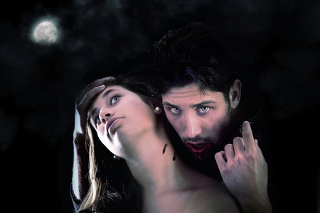 handsome vampire biting girl isolated in dark background