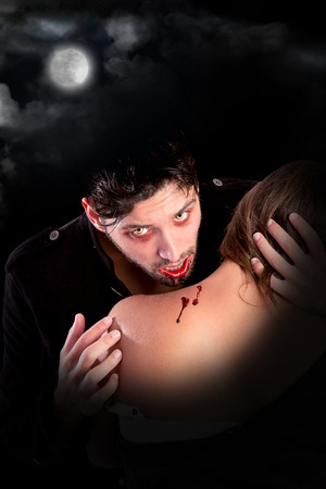 beautiful vampire: handsome vampire biting girl isolated in dark background