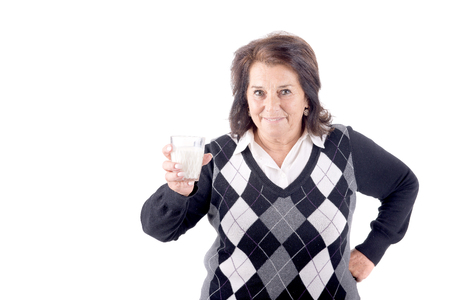 gracious: beautiful senior woman with glass of milk isolated in white Stock Photo