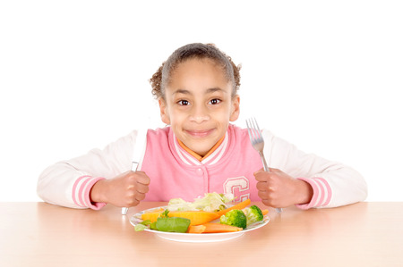children eating: little girl eating vegetables isolated in white background Stock Photo