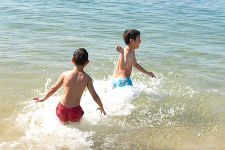 boardshorts: little kids posing at the beach Stock Photo