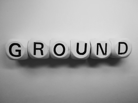 spelling of word ground using dice on white background