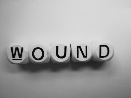 spelling of word wound using dice on white background