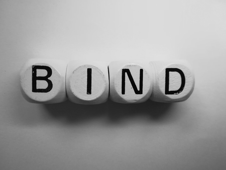 spelling of word bind using dice on white background