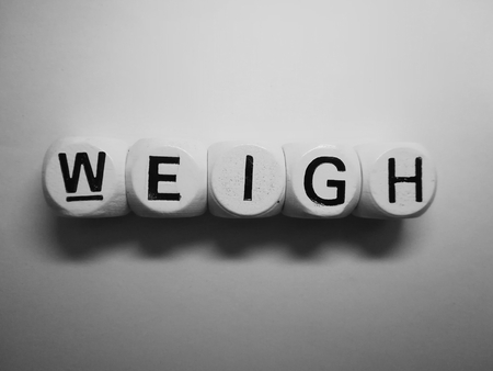 spelling of word weigh using dice on white background Stock Photo