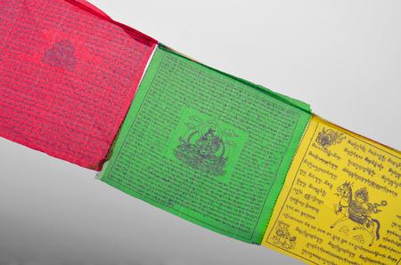Colorful Buddhism prayer flags (Dar Cho, lungta) wth Buddism symbols. Image of Green Tara, Close up.