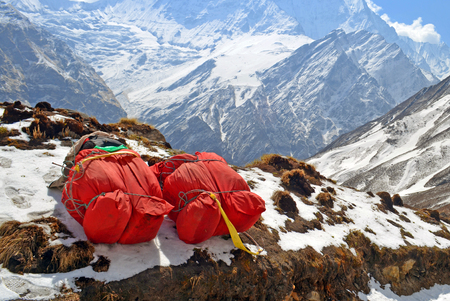 Two huge red backpacks for mountain expedition on snow. Porter Mountaineering equipment. Nepal, Annapurna Base Camp track.