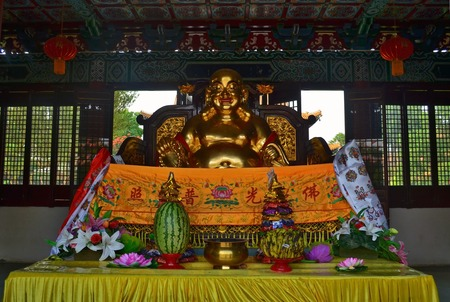 Golden Statue and offerings in Traditional Chinese Buddhist temple in Lumbini, Nepal - birthplace of Buddha Siddhartha Gautama.