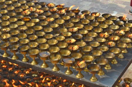 oil lamp: Many burning oil lighting up candles lamps in buddhist temple - Great stupa Bodnath in Kathmandu, Nepal. For ritual, meditation, consciousness, praying, faith.