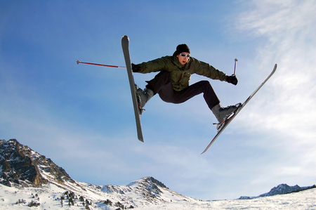Jumping alpine skier against the blue sky in mountains