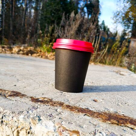 A black paper cup with a red lid for coffee stands on concrete against a background of grass and trees. Concept. Autumn background.