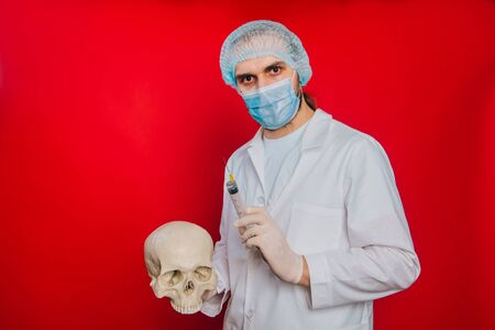 The doctor holds a skull and a syringe with a vaccine in his hands. A young guy in a white coat, in a medical mask and gloves on a red background. Pathologist medical worker. The concept of mortality
