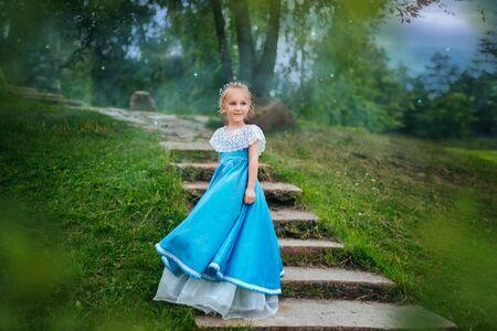 Bambina con i capelli bianchi in un abito retrò blu.