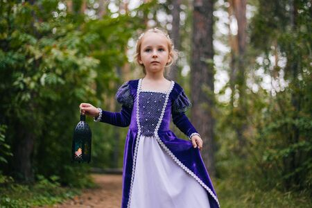 A little girl with white hair in a purple medieval dress stands with a lamp.