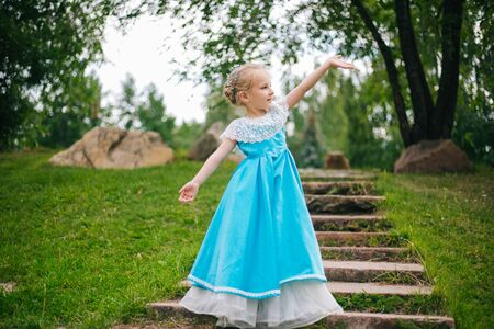 Little girl with white hair in a blue retro dress.