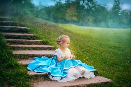 Little girl with white hair in a blue retro dress holds a small carriage in her hands.