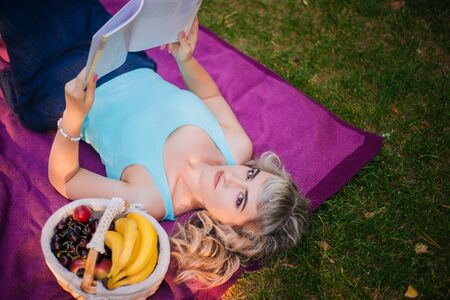 Beautiful girl on a picnic in the park is reading a book. Blonde on a purple bedspread resting.