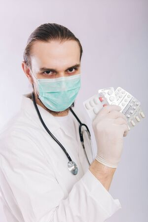 A doctor in a white coat, a medical mask and gloves holds pills. Types of drugs. Medical worker on a white background. Studio photo Banque d'images