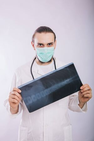 A doctor in a white coat and a medical mask holds in his hands pictures of lung X-ray on a white background. Examines X-ray pictures of a patient