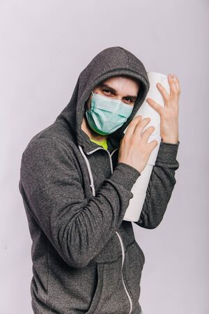 A guy in a gray sweatshirt and with rolls of toilet paper is standing on a white background. The excitement during quarantine for coronavirus.