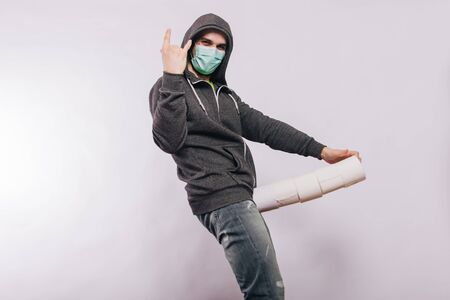 A guy in a gray sweatshirt on a white background in a medical mask holds a stack of toilet paper rolls in his groin.